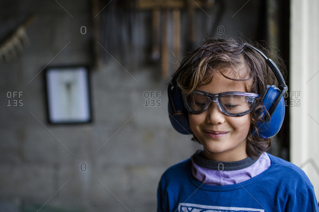 Smiling boy wearing protective workwear looking down while standing against wall in blacksmith shop