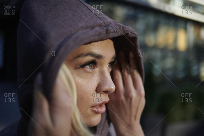 Close-up of thoughtful woman wearing hooded shirt exercising while standing outdoors during sunrise