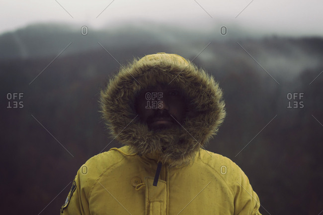 Close-up portrait of man wearing yellow fur coat standing outdoors during winter