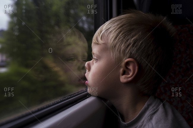 Side view of thoughtful boy looking through window while traveling in train