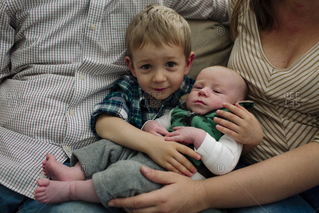 Portrait of cute boy carrying newborn brother while sitting between parents at home
