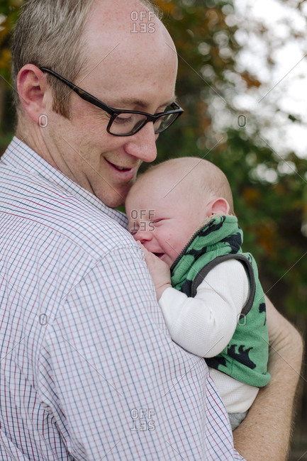 Side view of smiling father carrying cute newborn son while standing in park
