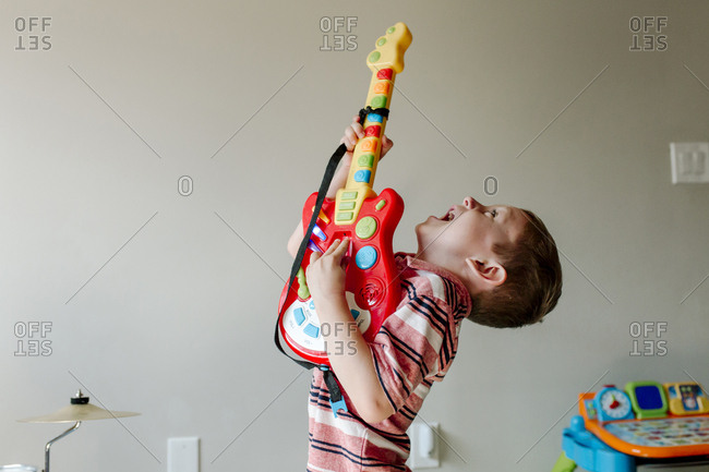 Cute happy boy singing while playing toy guitar against wall at home