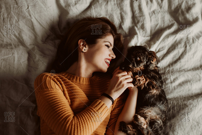 Portrait of woman playing with puppy on bed