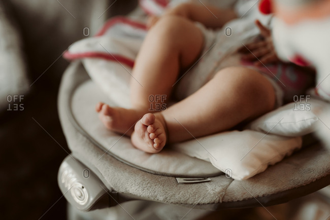 Close up of little baby with bare feet sitting in bouncer