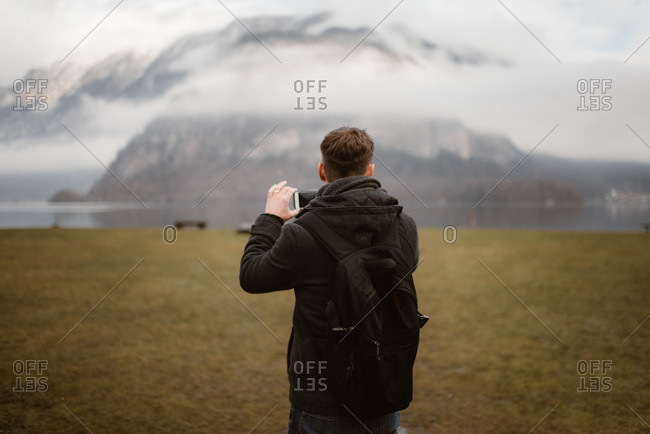 Man taking pictures of cloudy mountain landscape