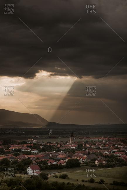 Sunlight peaking through dark clouds over town