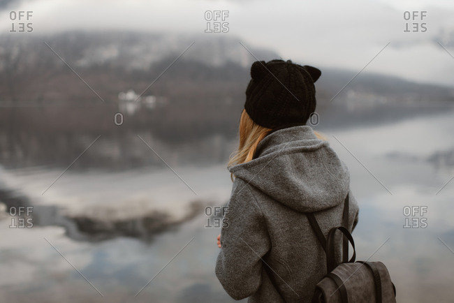 Woman looking out at a cloudy mountain landscape