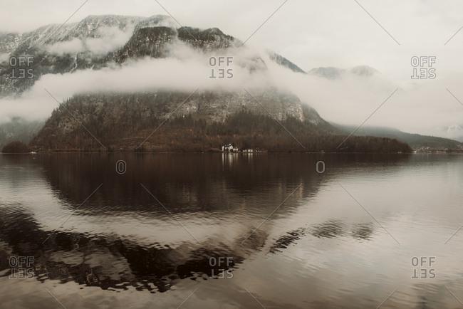 Clouds surround lakeside mountain