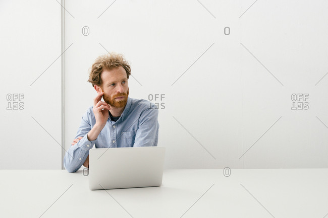 Thirty something bearded man looking thoughtfully on his laptop sitting at an empty light colored desk.