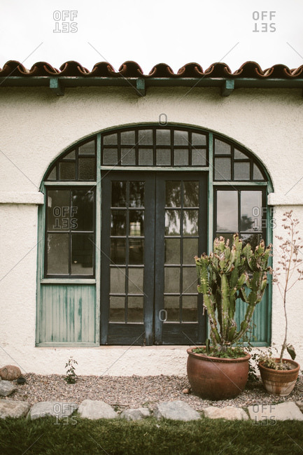 Adobe ranch doors with blue window frames and potted succulents