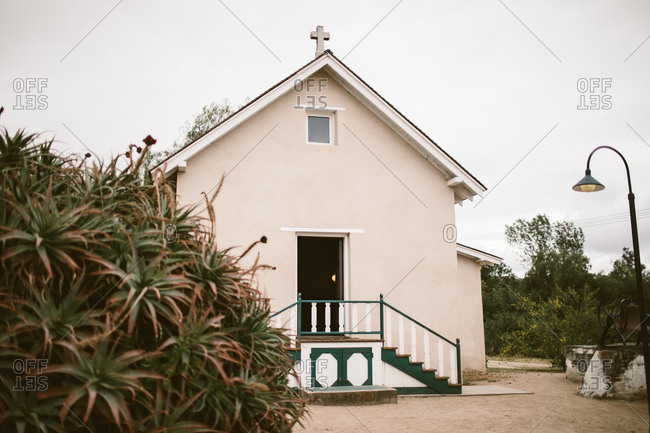 Old adobe ranch chapel with foliage and a small cross and an open door