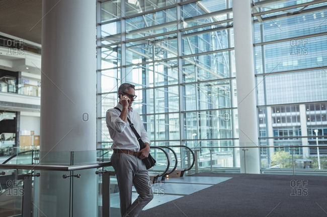 Side view of a businessman talking on the mobile phone in an empty modern office with a building background