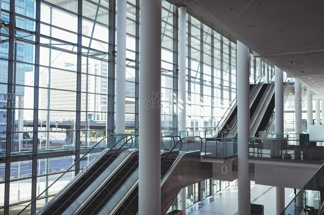 Side view of an empty modern buildings area with escalators, pillars and exterior glass wall with a city background