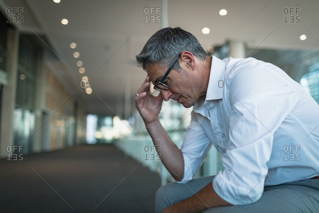 Close-up of frustrated businessman sitting in office corridor