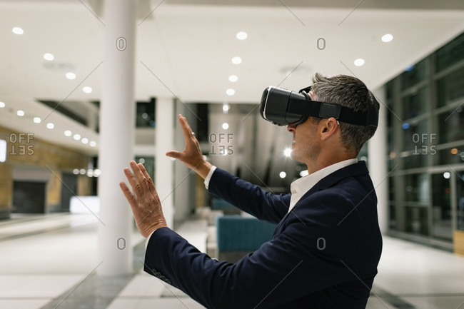 Side view of a businessman experiencing VR headset and raising his hands in the corridor in office by night