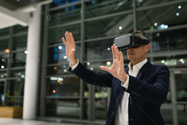 Front view of a businessman experiencing VR headset and raising his hands outside the office by night