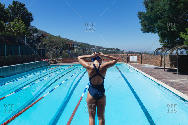 Rear view of young Caucasian female swimmer wearing swim goggle at swimming pool in the sunshine