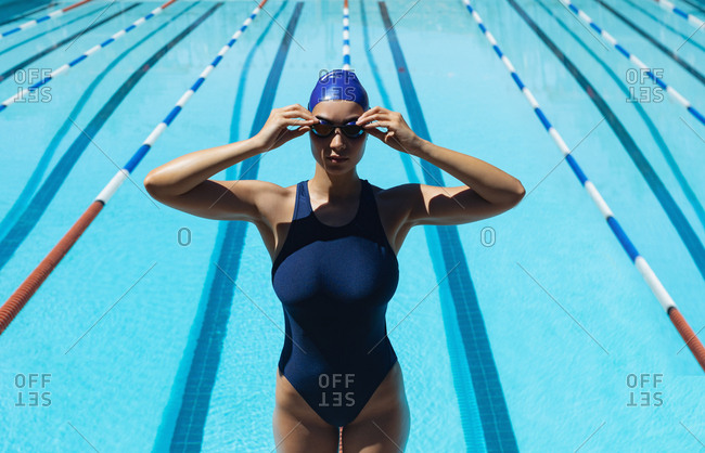 High angle view of young Caucasian female swimmer wearing swim goggle at swimming pool in the sunshine