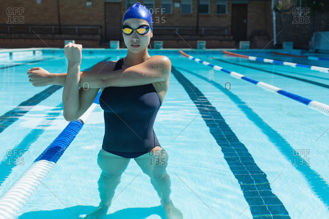 Front view of young female swimmer with swim goggle stretching at swimming pool