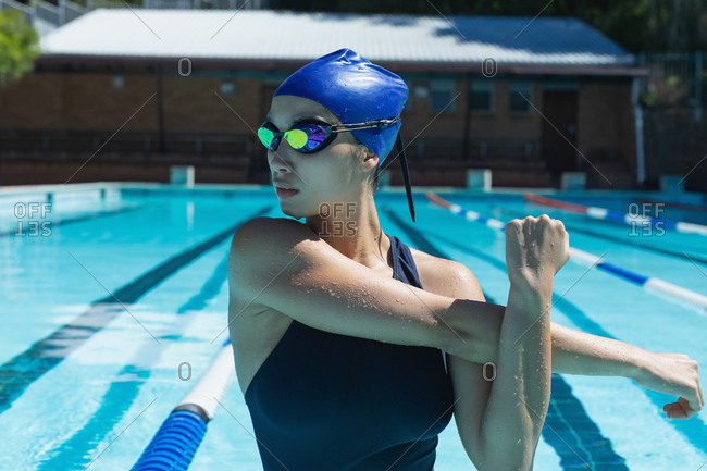 Front view of young female swimmer with swim goggles stretching in the swimming pool on a sunny day