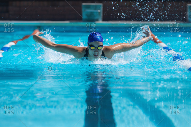 Front view of young female swimmer with swim goggle swimming at swimming pool