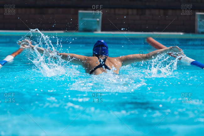 Rear view of young female swimmer with swim goggle swimming at swimming pool