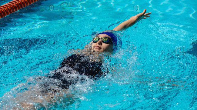 High angle view of young female swimmer swimming backstroke in swimming pool