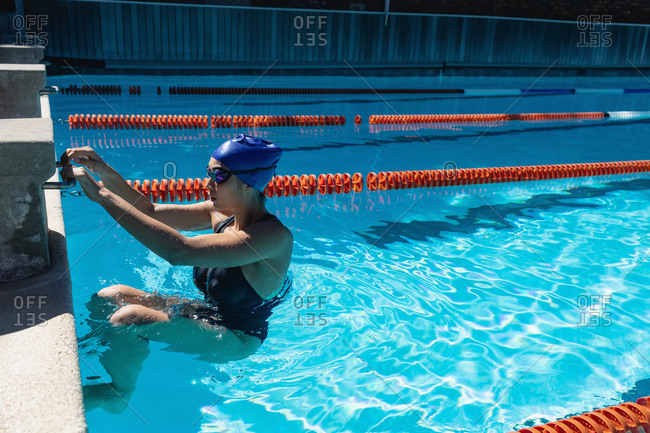 Side view of young female swimmer swimming in swimming pool