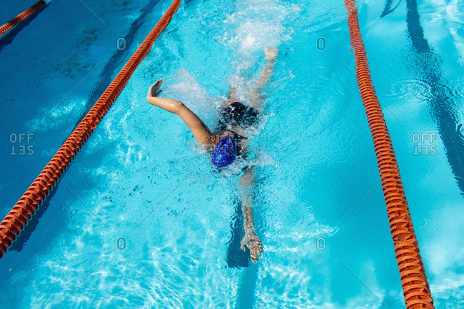 Young female swimmer swimming freestyle in swimming pool