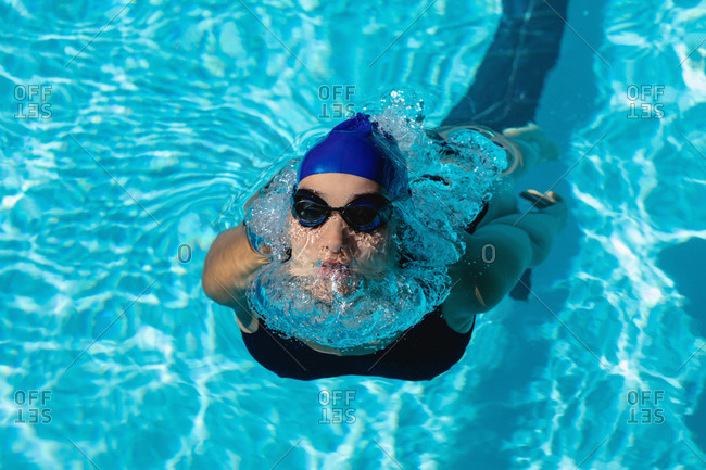 High angle view of young female swimmer swimming freestyle in swimming pool