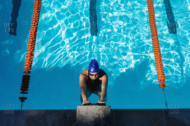 Overhead high view of a young female swimmer hanging at the handle of the starter block in swimming pool on a sunny day
