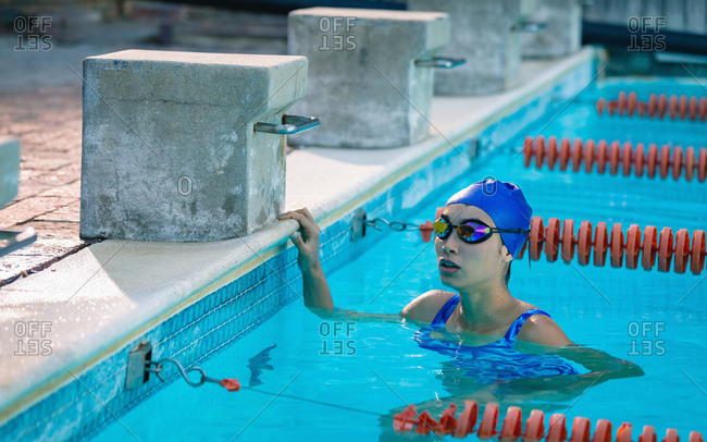 Front view of a tensed female swimmer waiting for the results in the swimming pool