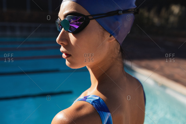 Close-up of female swimmer with swim goggles near swimming pool