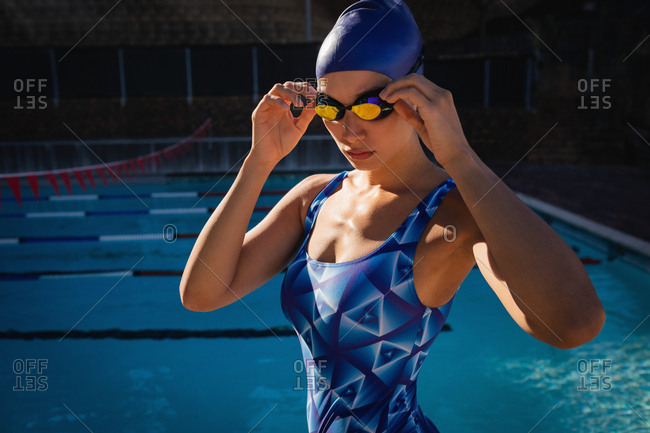 Front view of female swimmer wearing swim goggle and standing near swimming pool