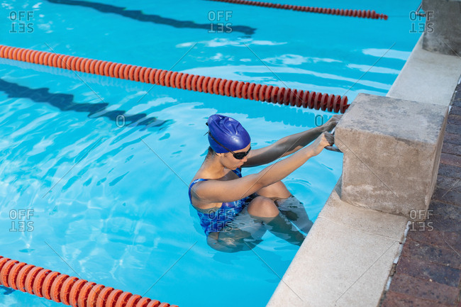 High angle view of female swimmer hanging on the starting block handle in swimming pool