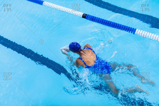 High angle view of female swimmer swimming breaststroke in swimming pool