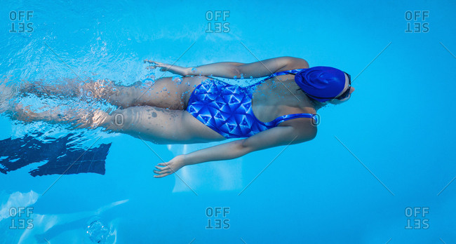 Overhead view of female swimmer swimming freestyle in swimming pool