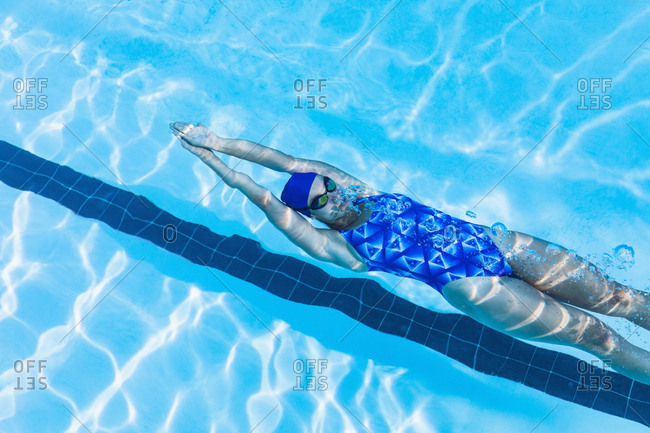 High angle view of female swimmer swimming backstroke in swimming pool