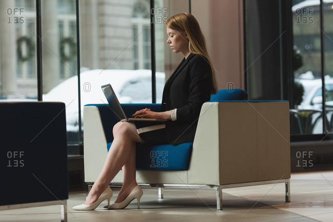 Side view of businesswoman using laptop in the lobby at office