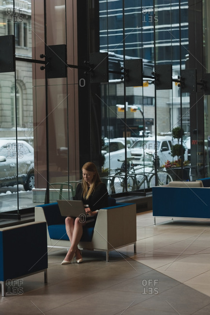 Far sight of businesswoman using laptop in the lobby at office