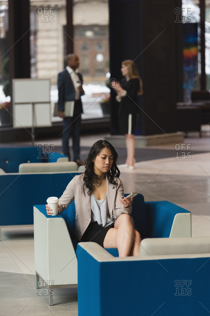Distant view of businesswoman using mobile phone in the lobby at office