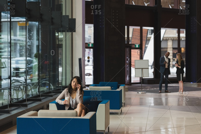 Distant view businesswoman talking on mobile phone in the lobby at office