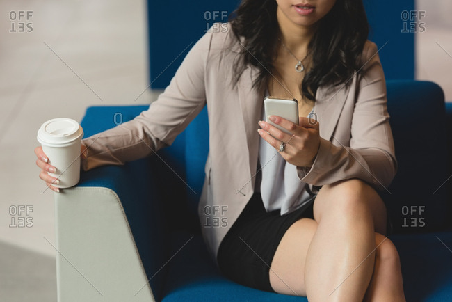 Mid section of businesswoman using mobile phone in the lobby at office