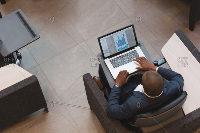 Top view of businessman using laptop sitting in the lobby at modern office