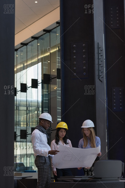 Side view of group of architects discussing over blueprint in the modern office. They are equipped with safety helmets