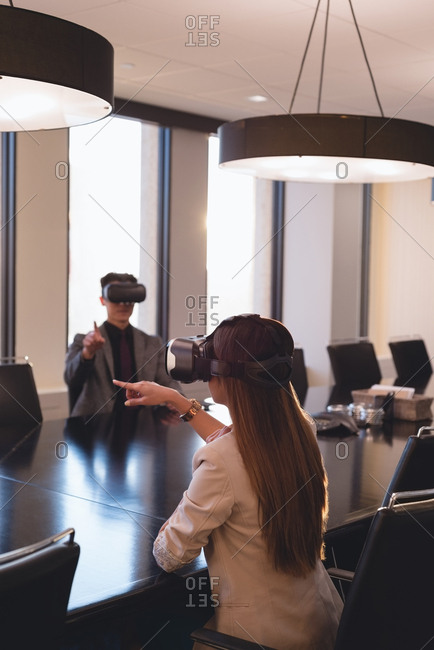 Rear view of business people using VR headset in the conference room at office