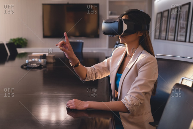 Side view of businesswoman using VR headset in the conference room at office