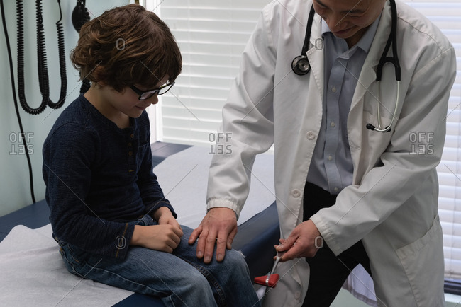 Front view of young asian male doctor examining caucasian boy patient knee in a clinic. Male doctor using reflex hammer