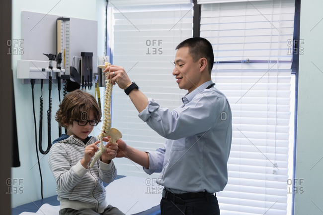 Side view of young asian male doctor showing vertebral column model to Caucasian boy patient